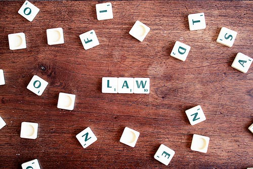 Board game pieces spelling 'law'